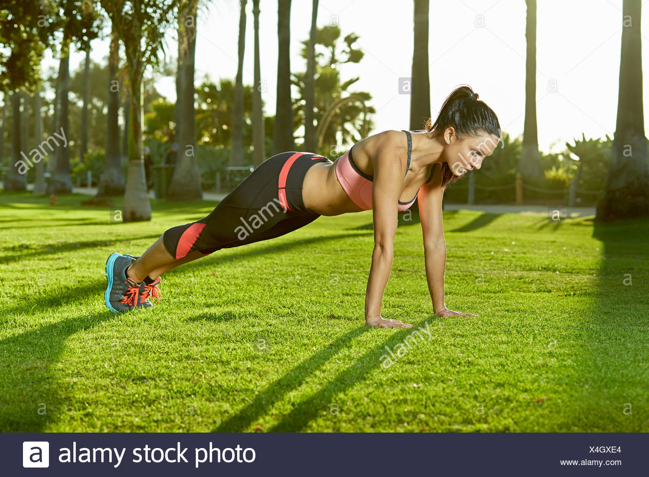 Mid adult woman doing plank exercise - Stock Image