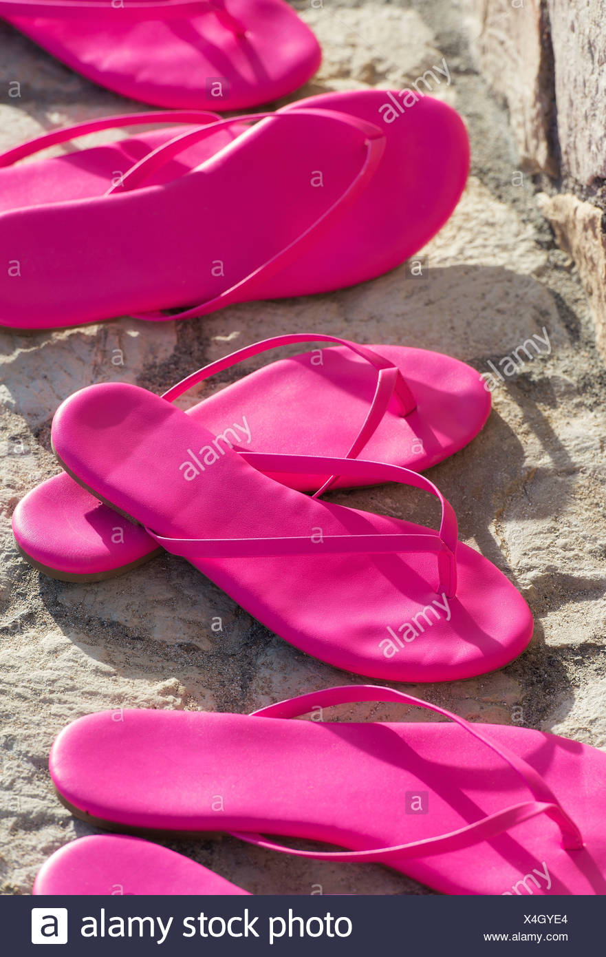 Matching pairs of hot pink sandals. - Stock Image
