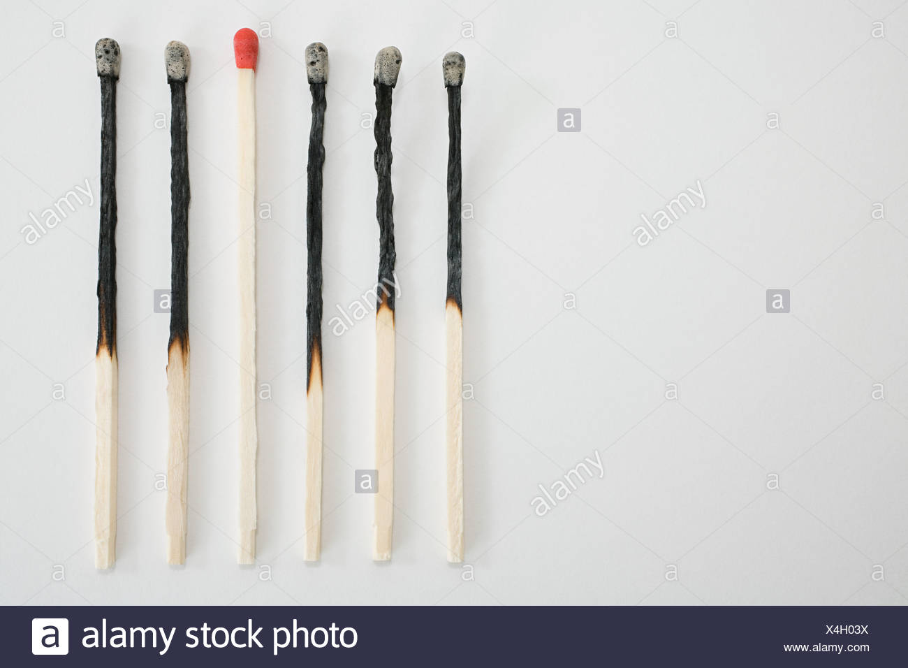 An unlit and burnt matches in a row - Stock Image