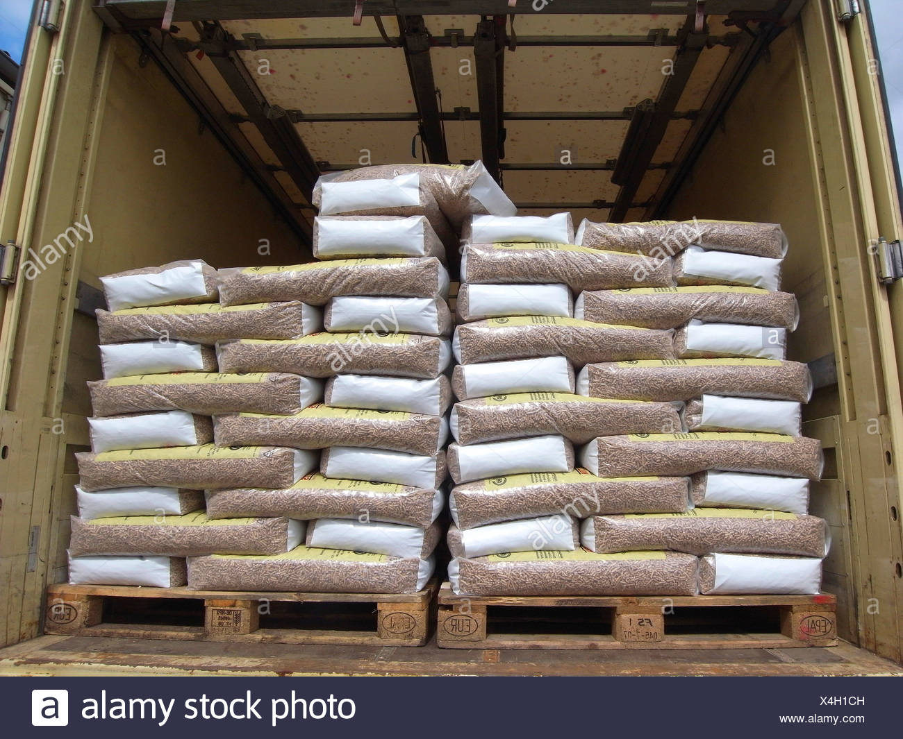 sacs of wood pellets in the cargo hold of a van - Stock Image