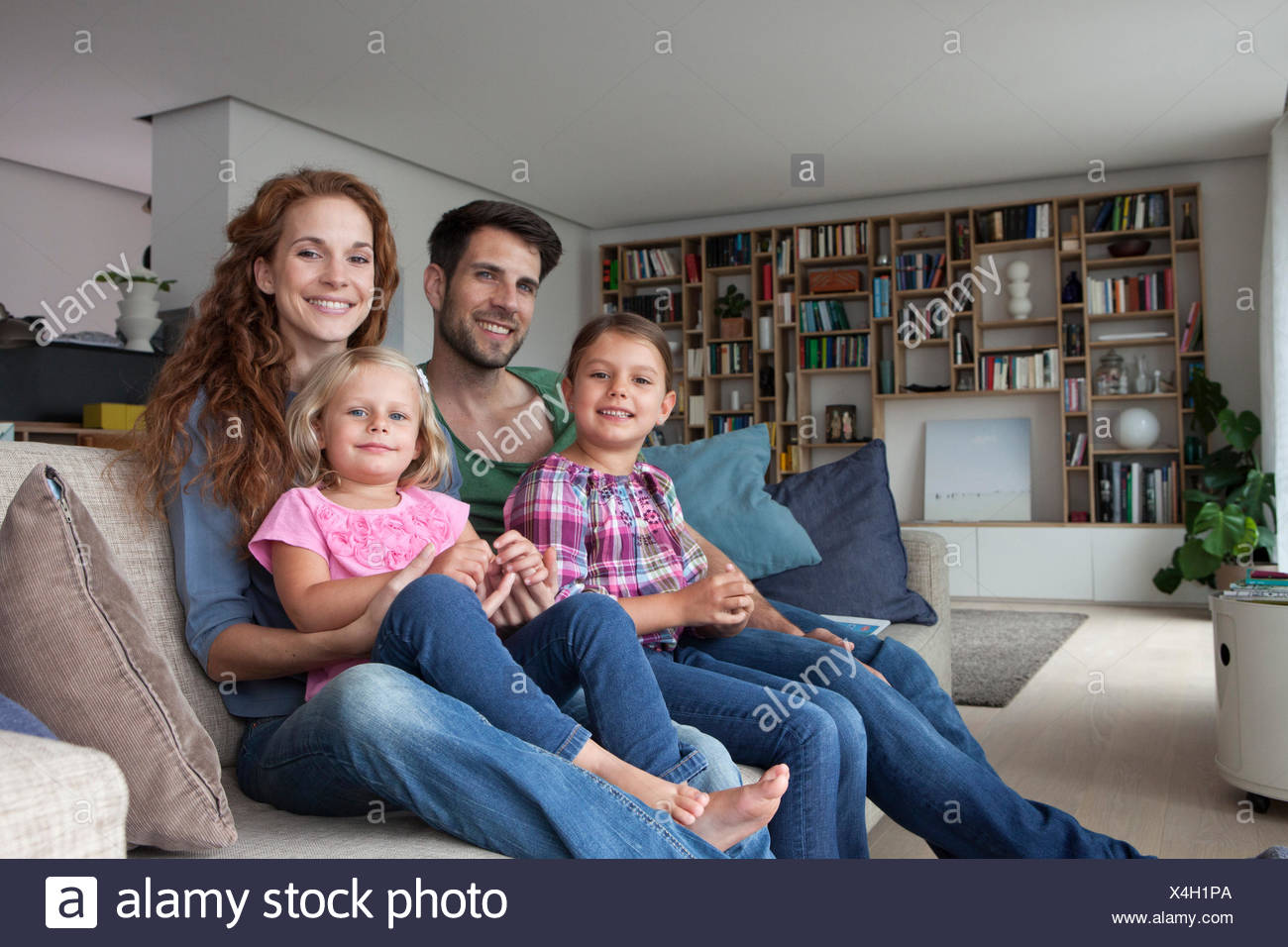 Family portrait of couple with two little girls sitting together on couch in the living room Stock Photo