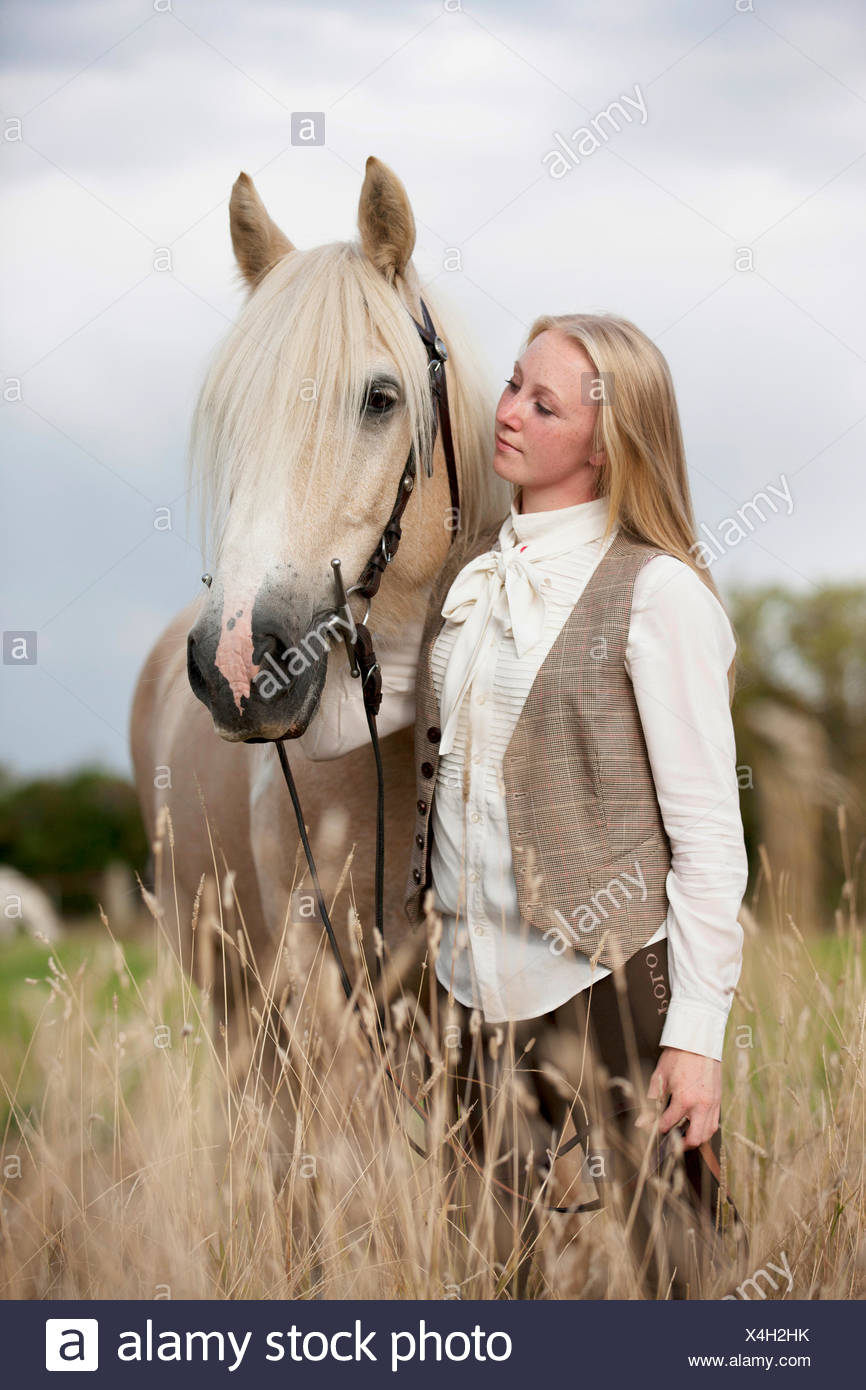 A young woman holding a palomino horse - Stock Image
