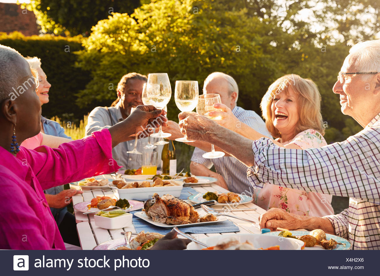 Group Of Senior Friends Making A Toast At Outdoor Dinner Party - Stock Image