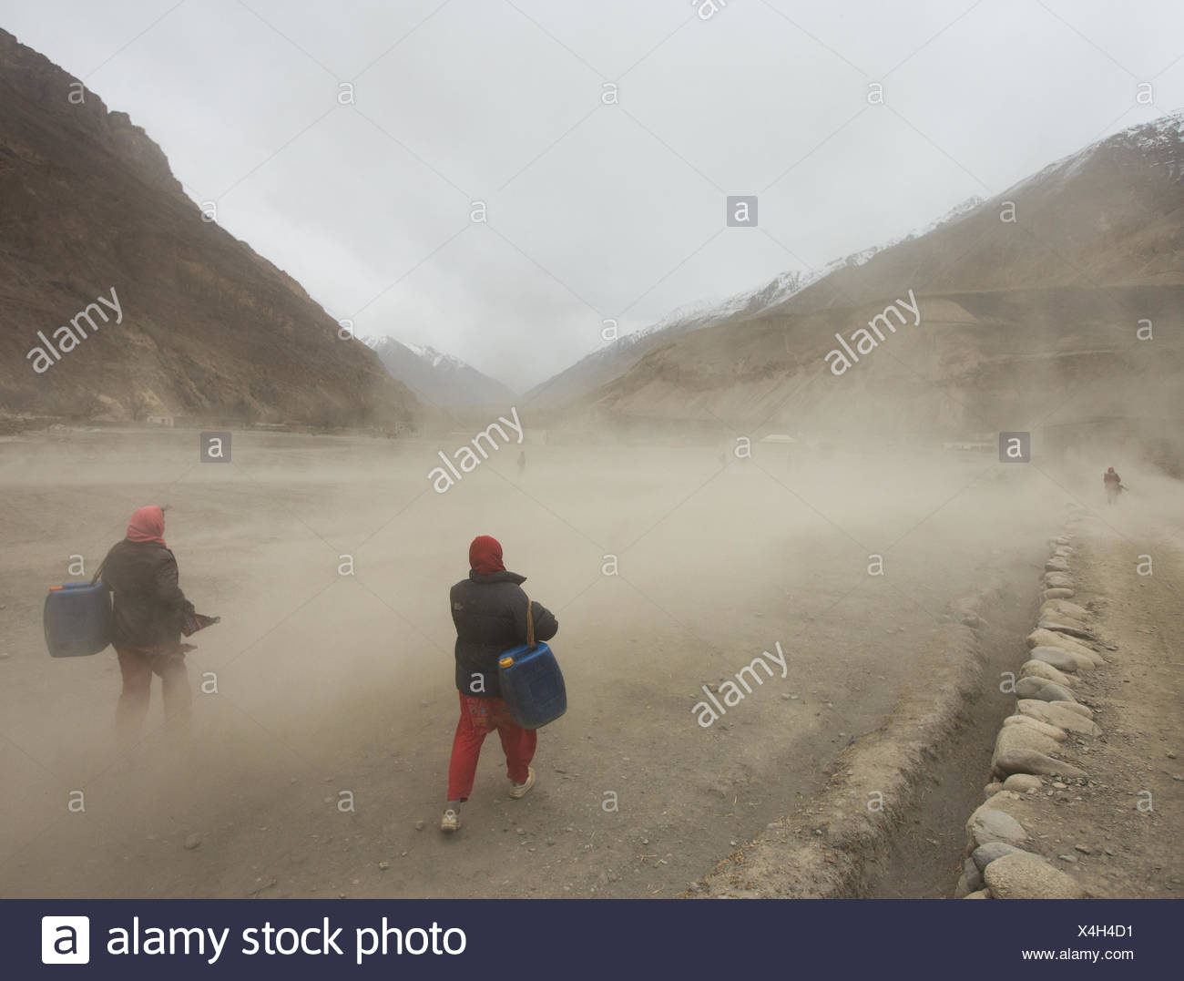 Women getting water in Shimsal, one of the remotest villages in the Karakoram mountains. - Stock Image