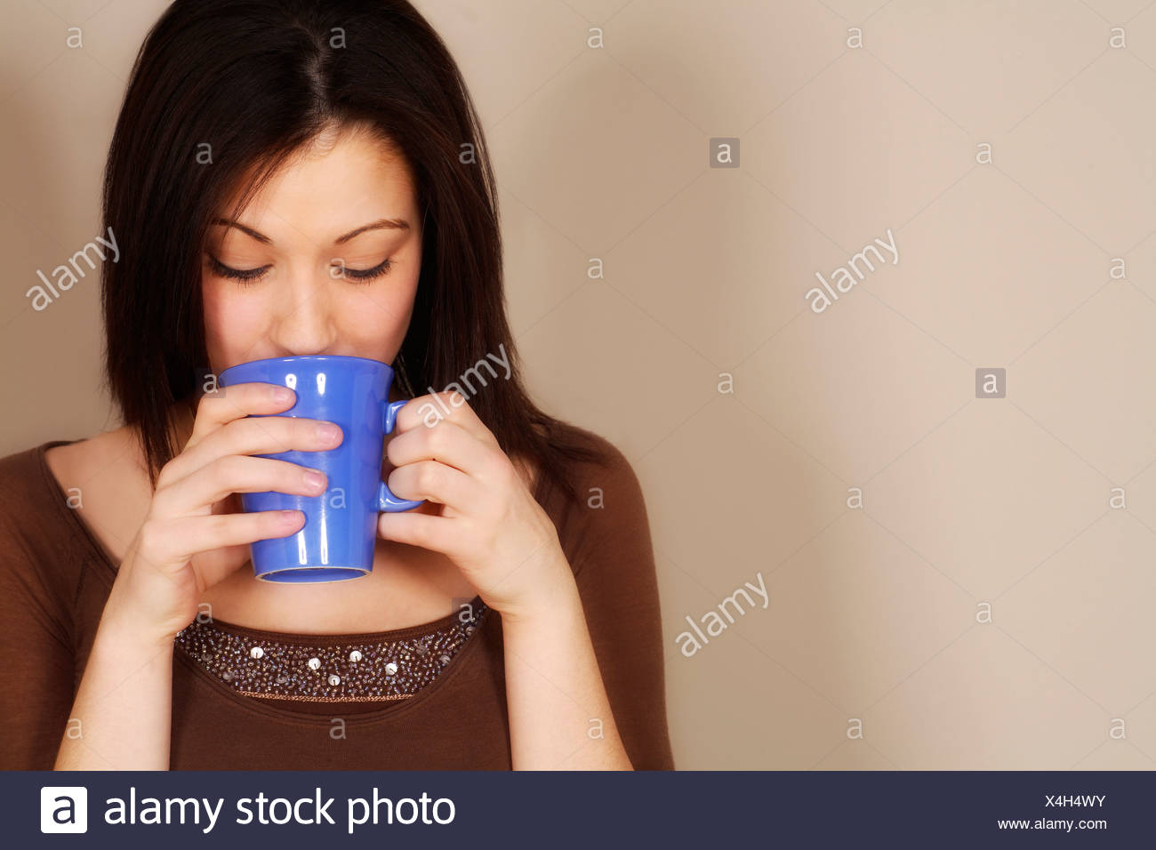 Woman drinking a hot drink - Stock Image