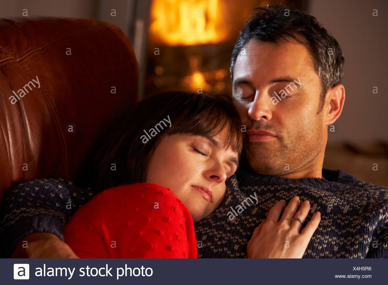 Middle Aged Couple Cuddling On Sofa By Cosy Log Fire Stock Photo