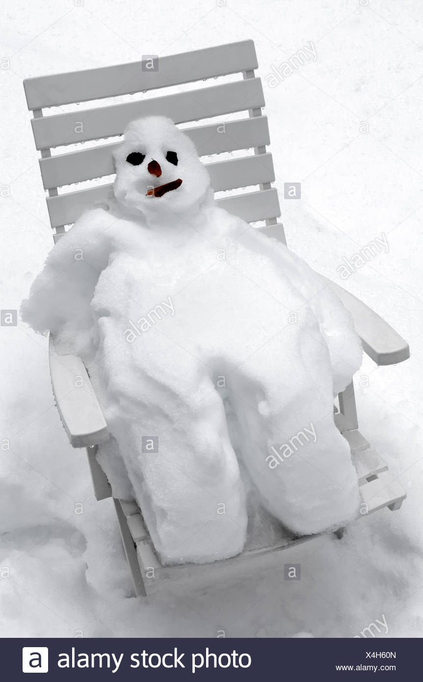 Snowman sitting on a white deck chair, relaxing - Stock Image