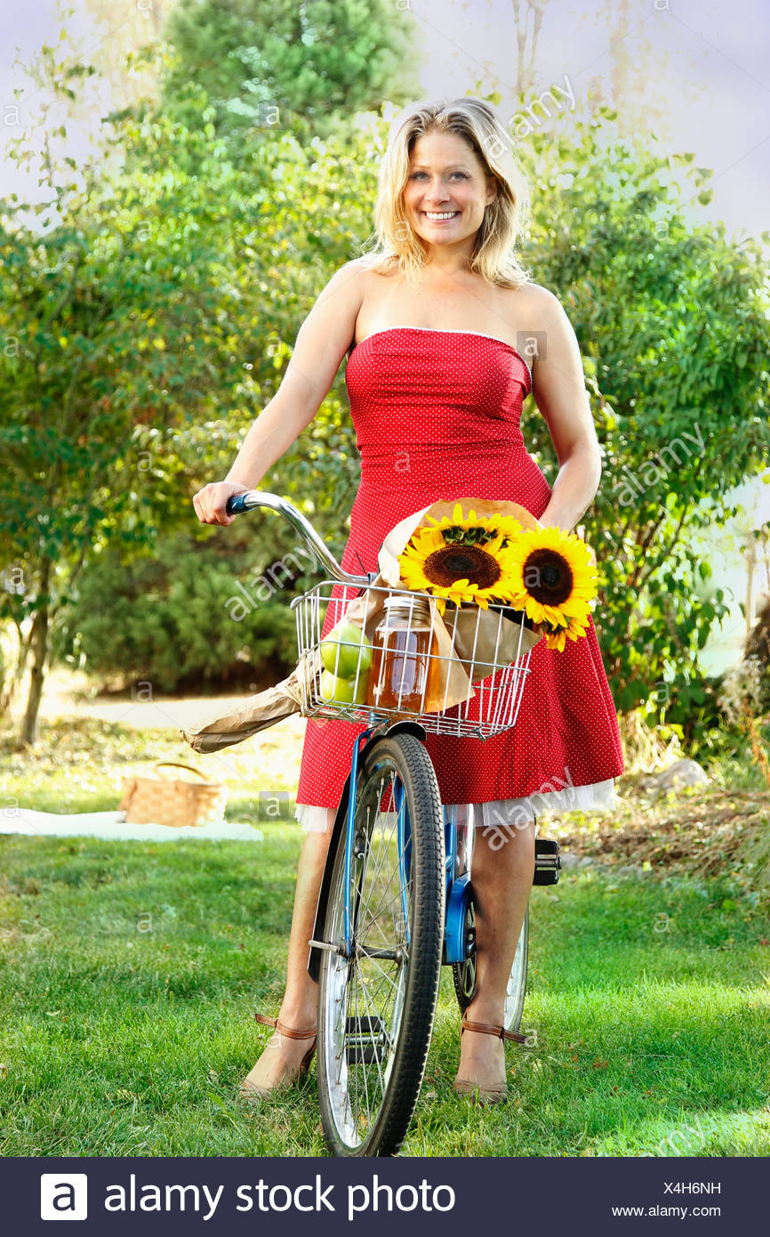 Woman standing with bicycle on grass - Stock Image