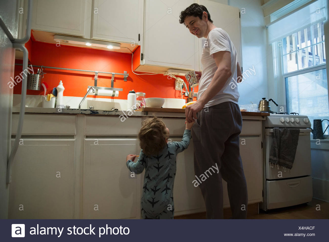 Father and son holding hands in kitchen - Stock Image