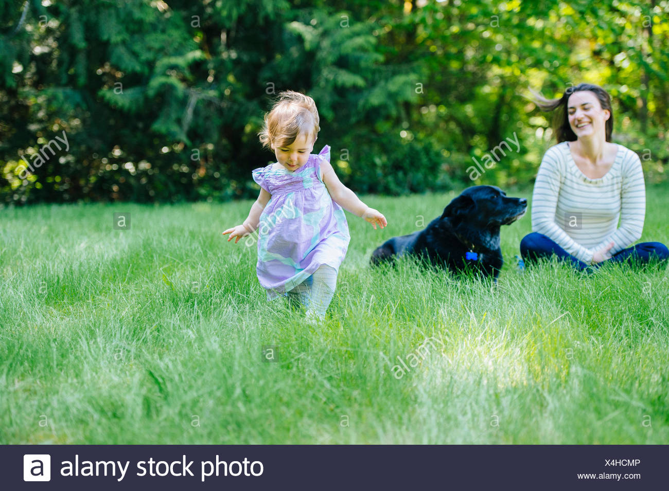 Female toddler running away from mother in park Stock Photo