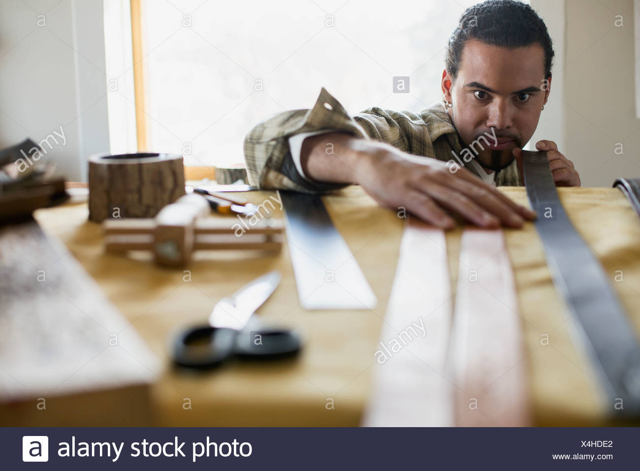 Man examining belts at leather workshop - Stock Image