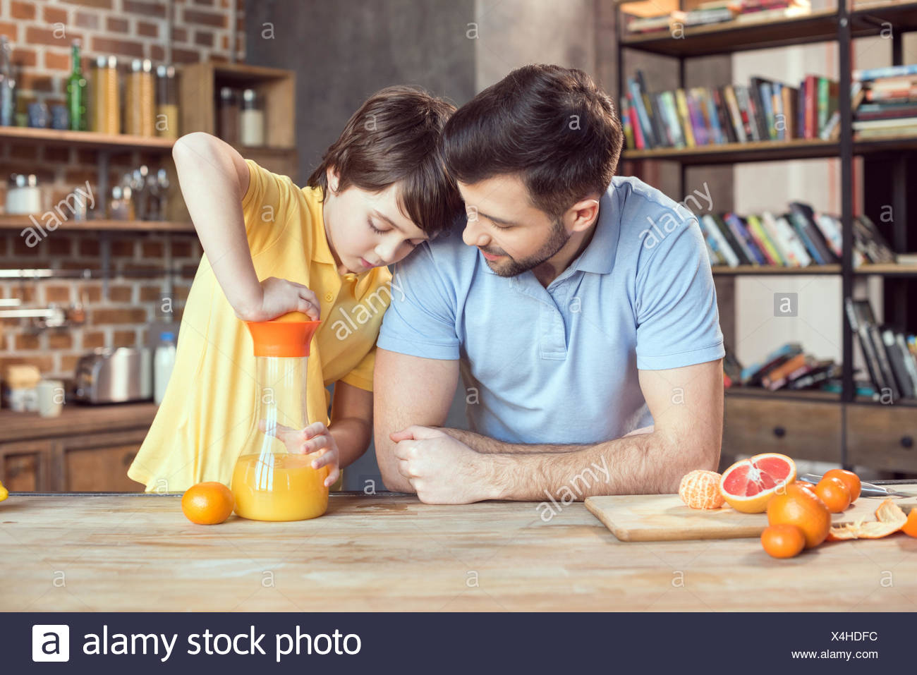 Father and son squeezing fresh orange juice at kitchen table - Stock Image