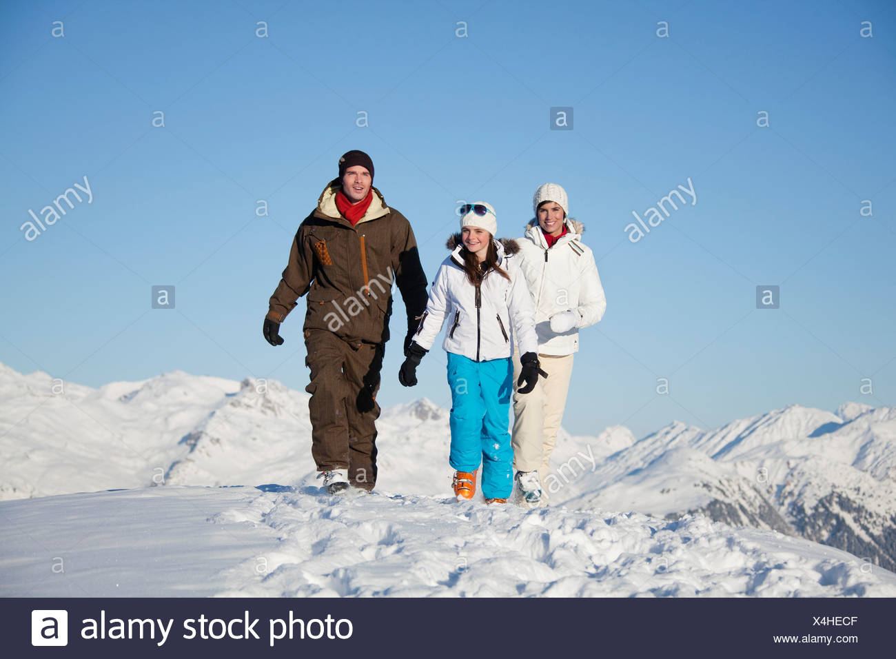 Couple and daughter in ski wear walking in snow - Stock Image