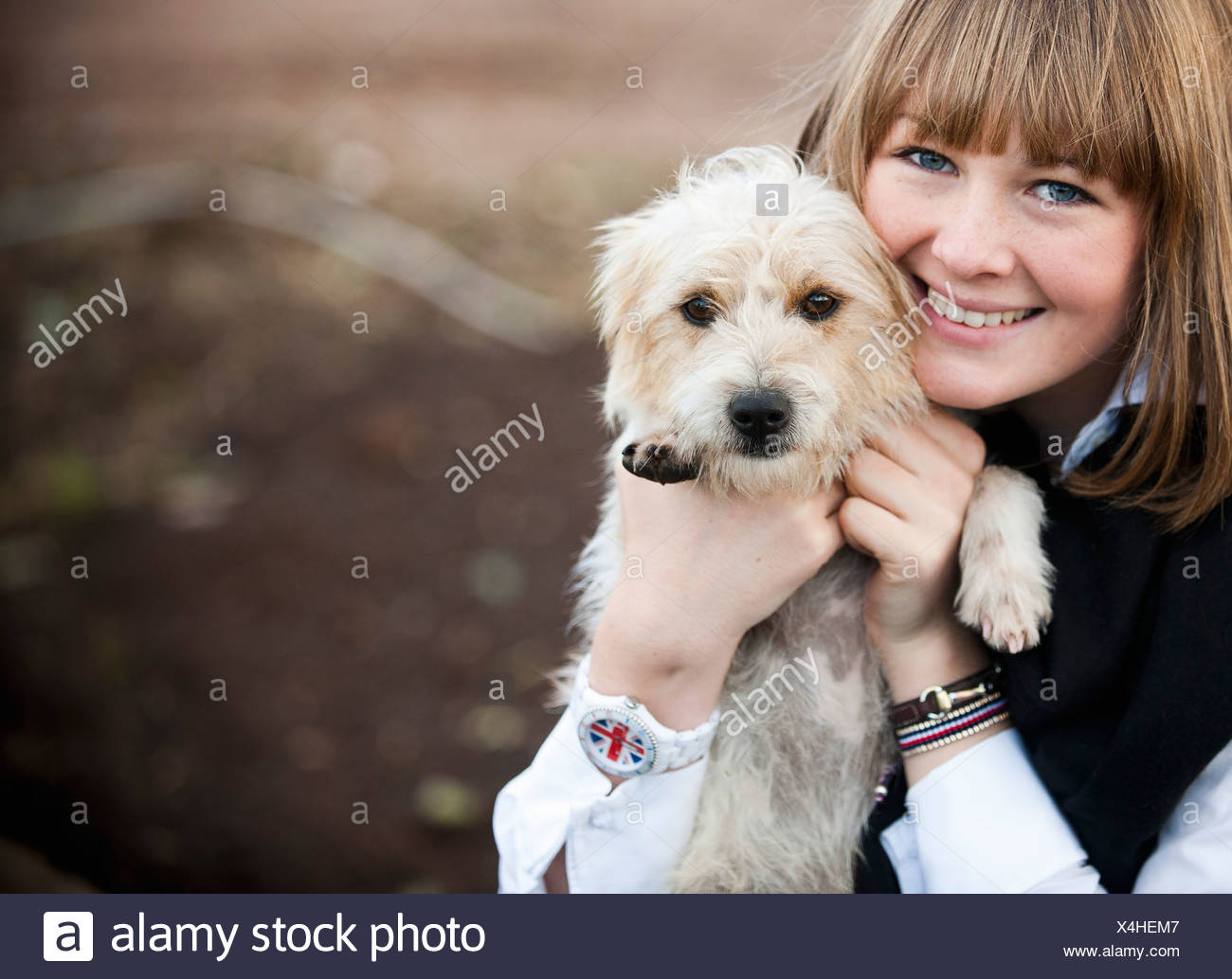 A woman hugging a small hairy terrier puppy. - Stock Image