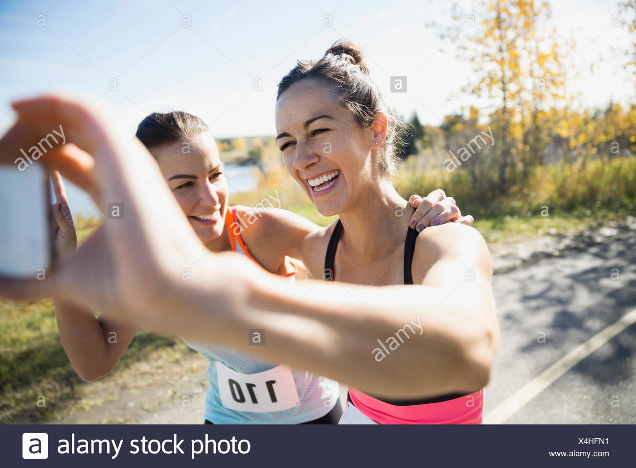 Laughing runners taking selfie on sunny path - Stock Image