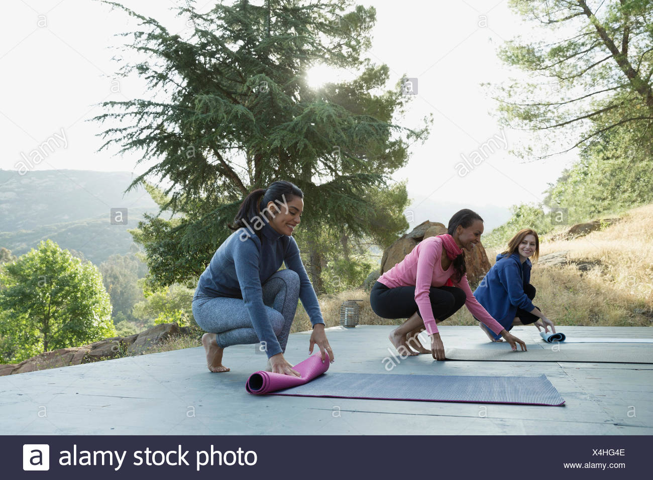 Women rolling up yoga mats after class on deck - Stock Image