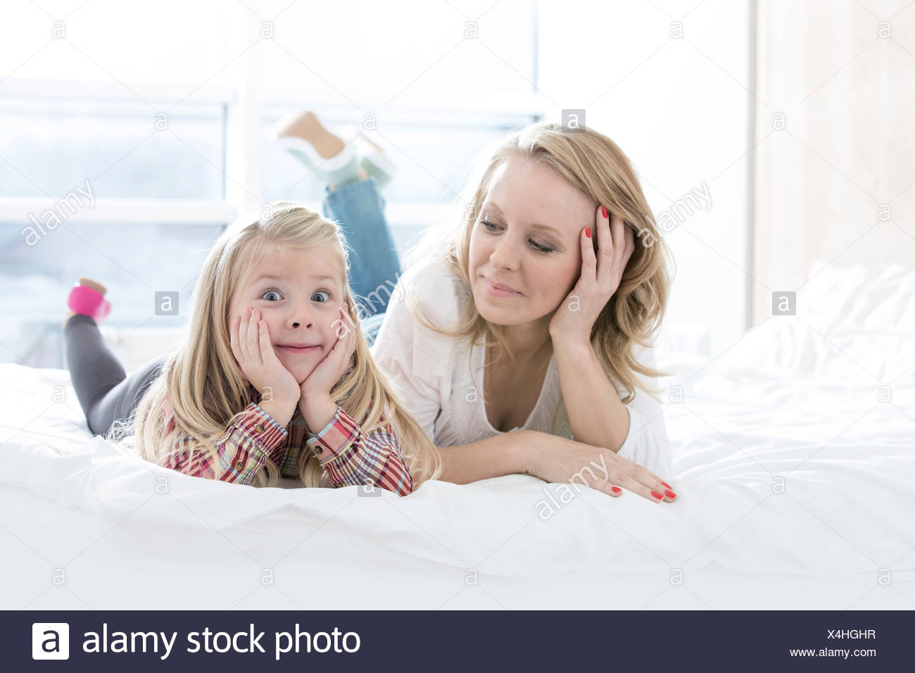 Mother looking at cute daughter making faces while lying in bed - Stock Image