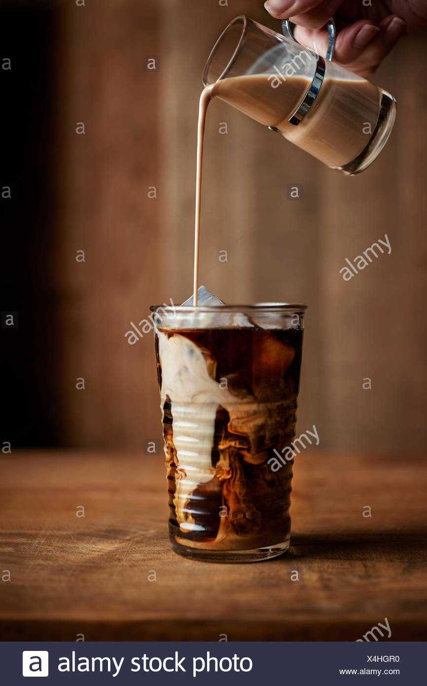 Glass of iced coffee with vintage creamer pouring into the glass on warm wood tones. - Stock Image