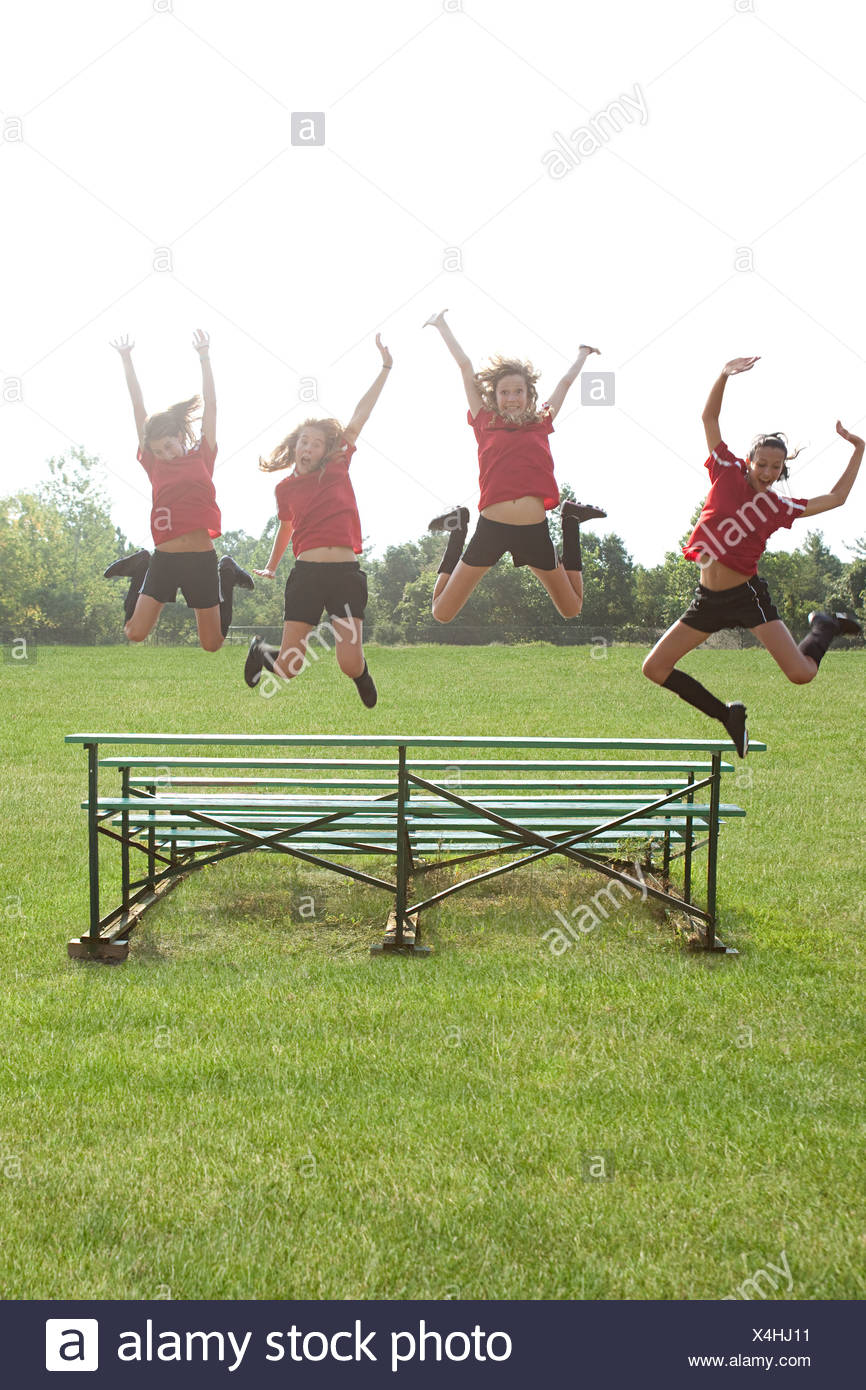 Girl soccer players jumping off bleachers - Stock Image