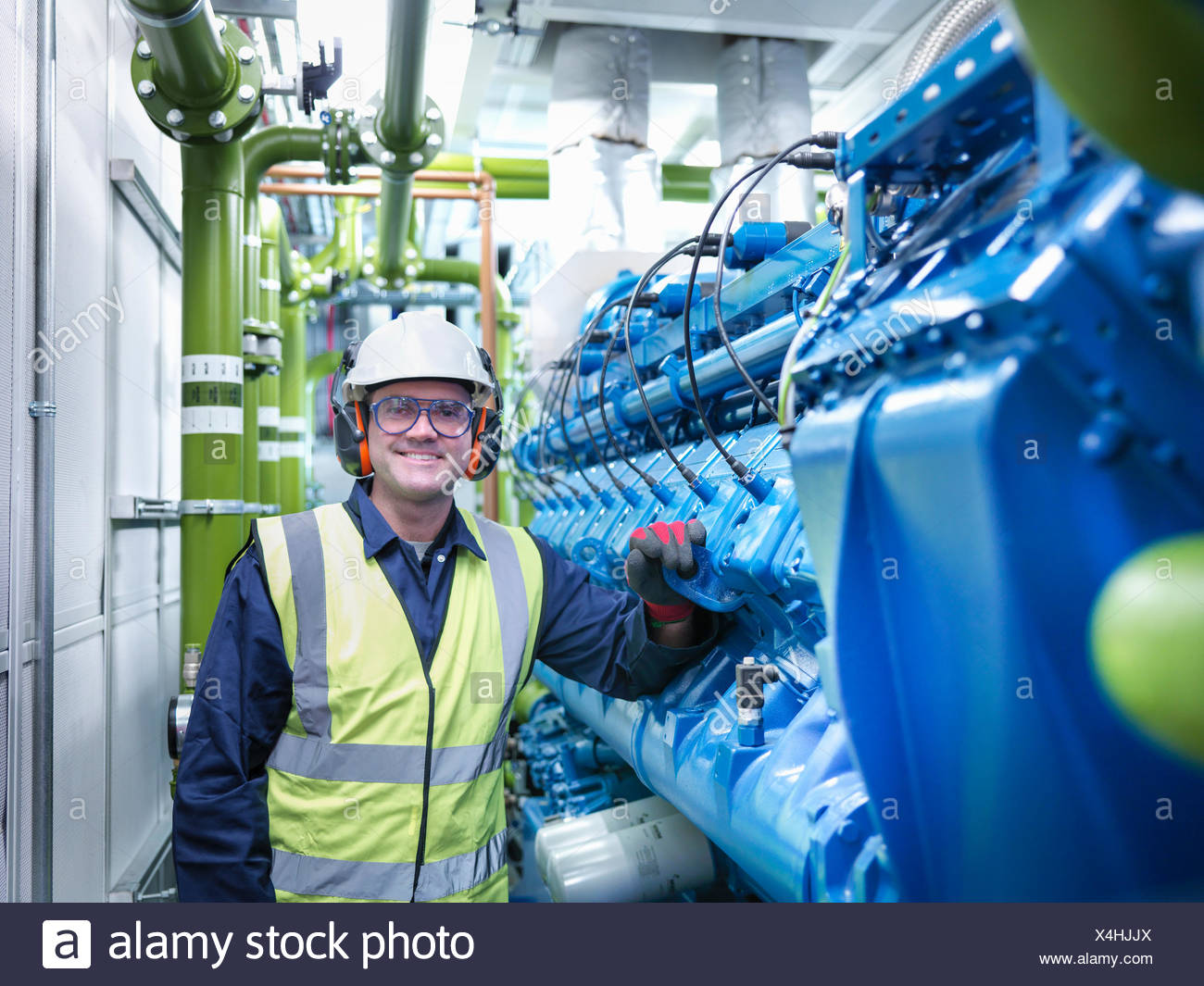 Worker with gas fired generator in gas fired power station - Stock Image