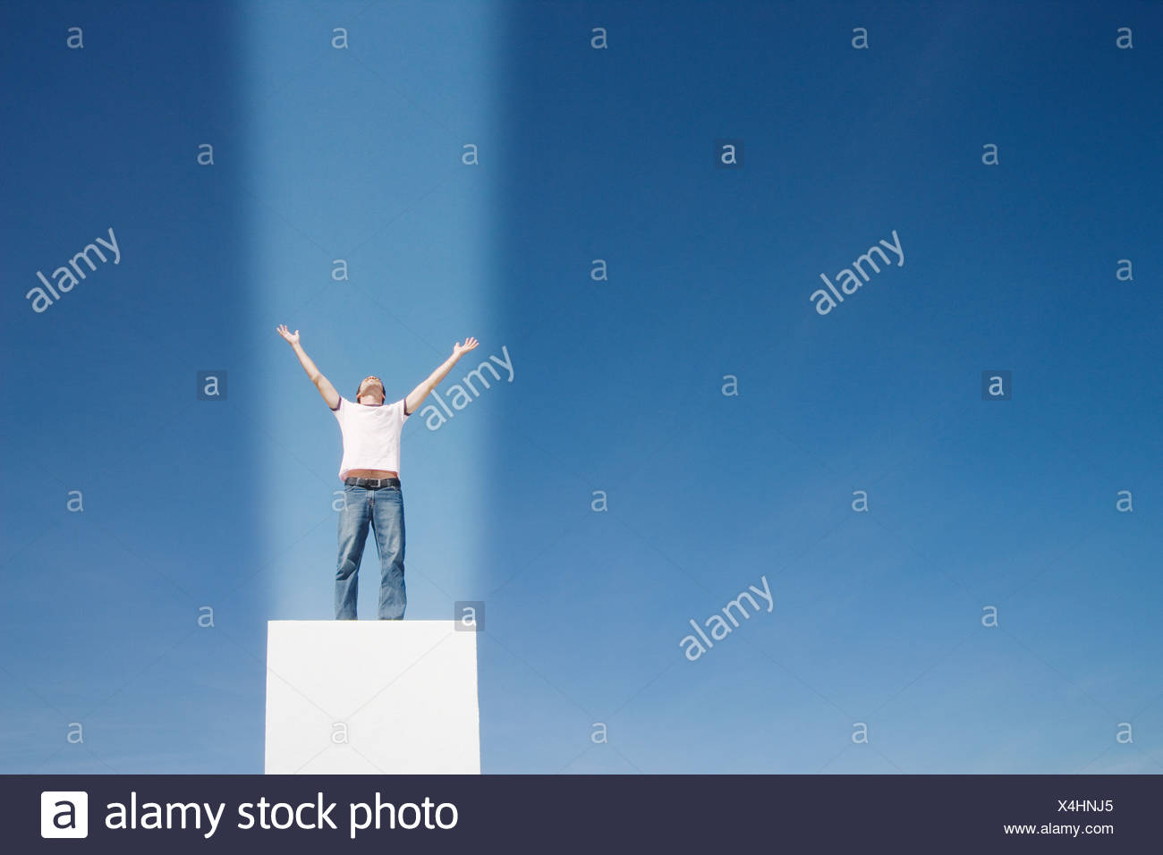 Man with a beam of light shining straight onto him - Stock Image