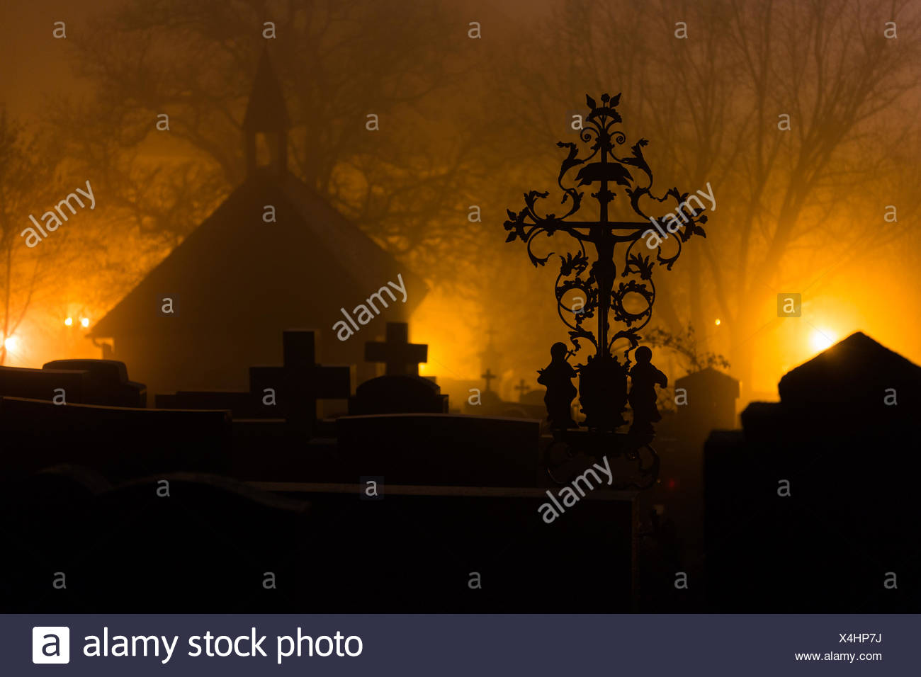 Silhouette Cemeteries At Graveyard Against Trees During Foggy Weather At Night - Stock Image