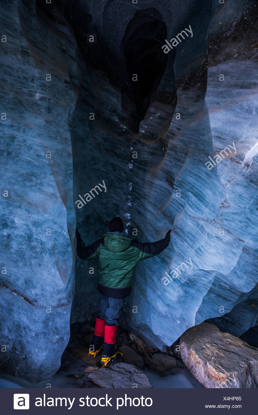 A man stands beneath an opening in the ice of Augustana Glacier where water empties from the glacier's drainage system during the melting season - Stock Image