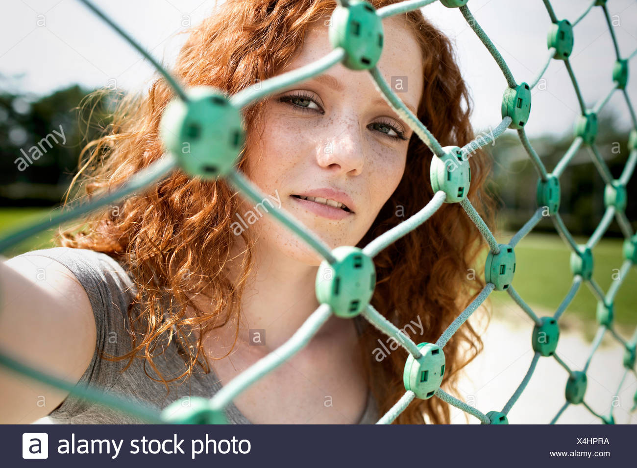 Portrait of redheaded teenage girl looking through net Stock Photo