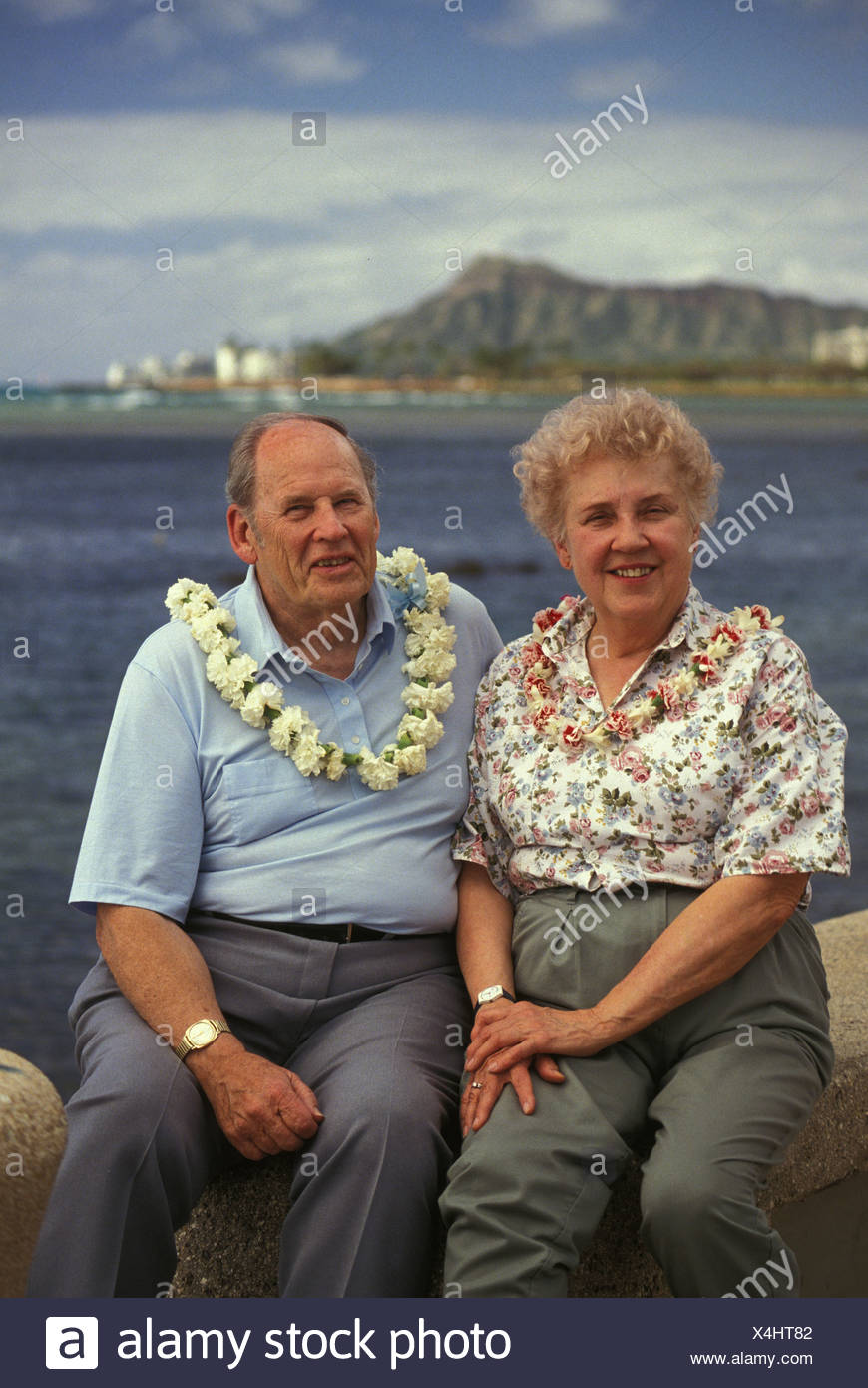 retired couple wearing flower lei at Kakaako Waterfront Park, with Diamond Head in the distance - Stock Image