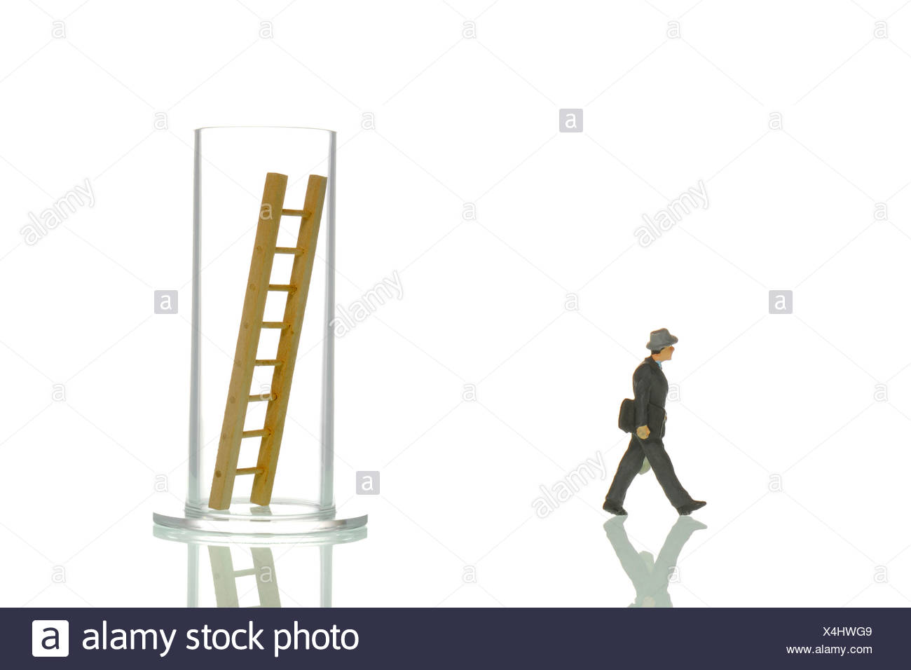 Manager figurines and glass with ladder, symbolic image for 'Breaking out of everday life' - Stock Image