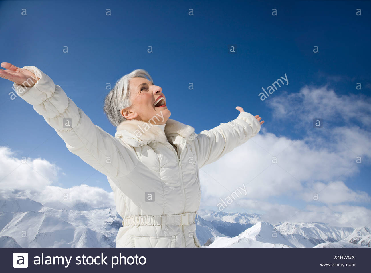 Mature woman with arms wide open on winter day Stock Photo