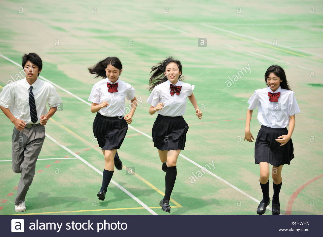 High School Students Running in the Schoolyard - Stock Image