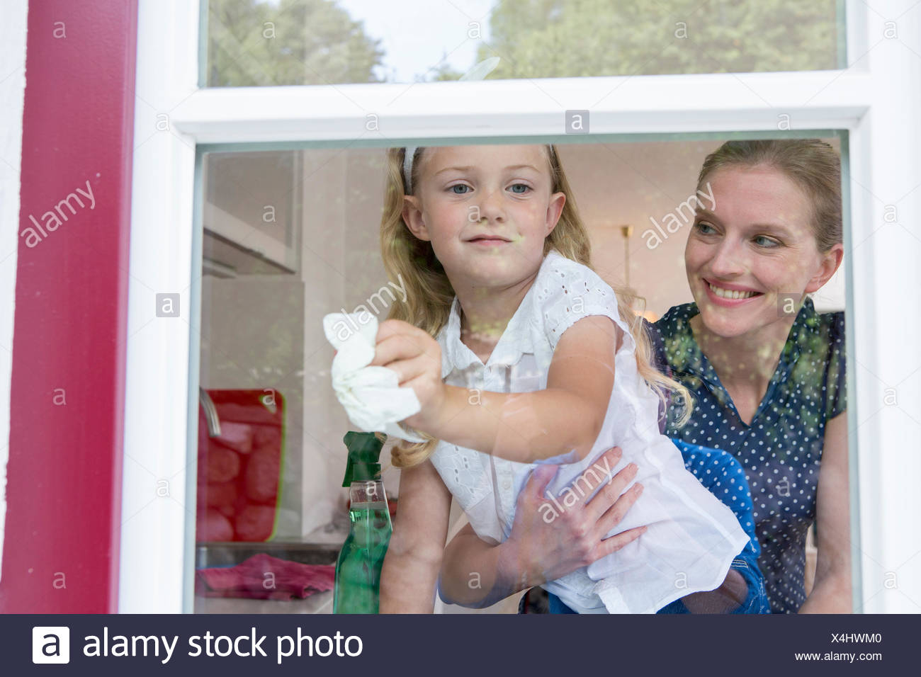 Mother and daughter cleaning window - Stock Image