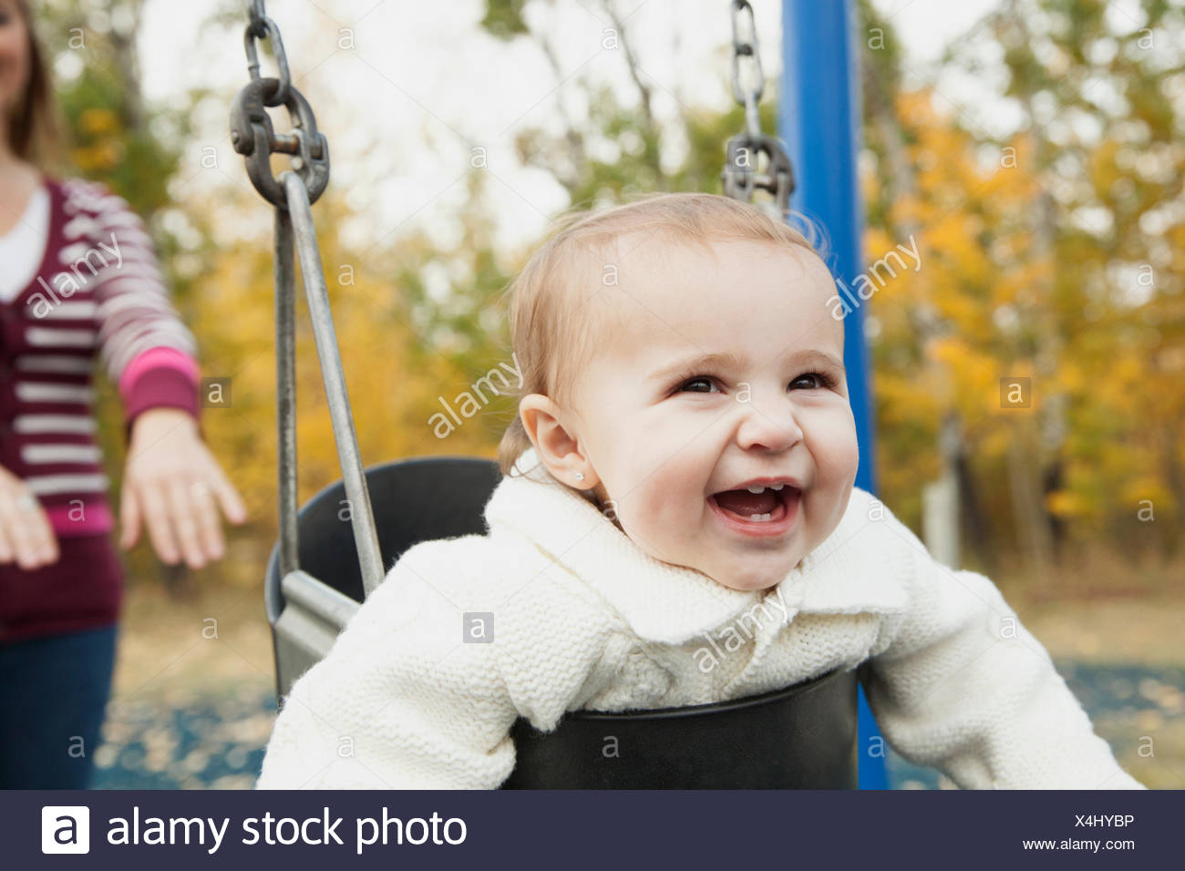 Mother pushing baby girl on swing in park - Stock Image
