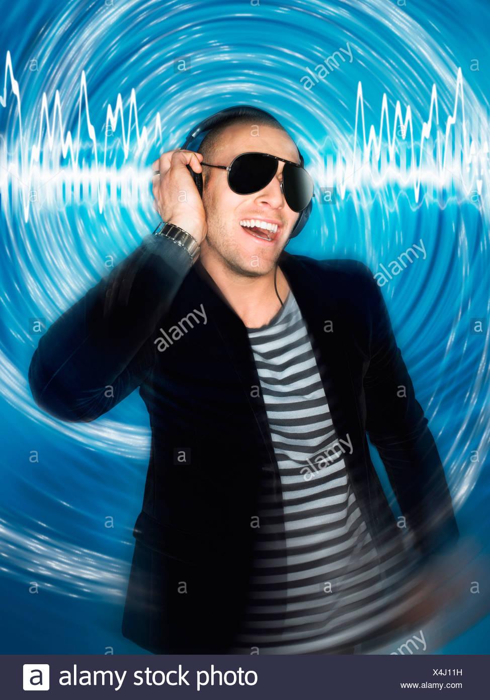 Man wearing headphones in front of circular effect, half-length - Stock Image