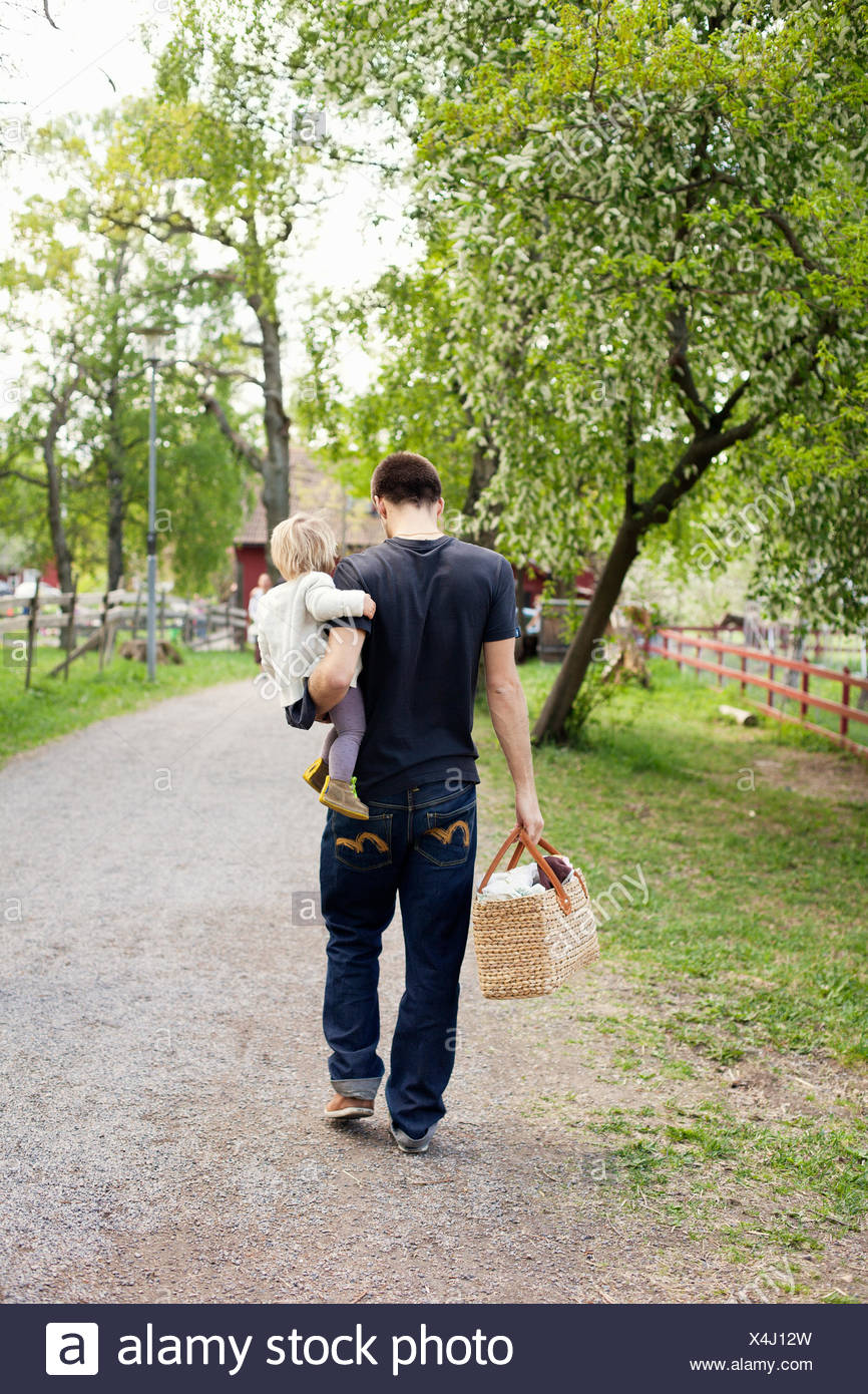 Sweden, Uppland, Father walking with daughter (18-23 months) - Stock Image