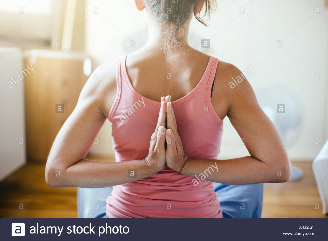 Rear view of mid adult woman in yoga position on bedroom floor - Stock Image