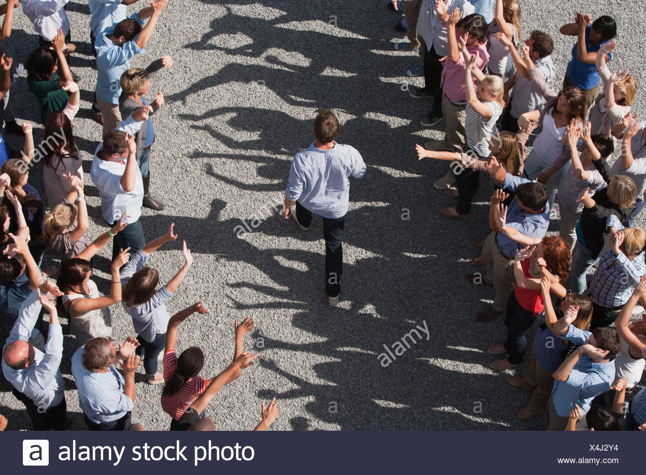 Man walking between two groups of people, elevated view - Stock Image