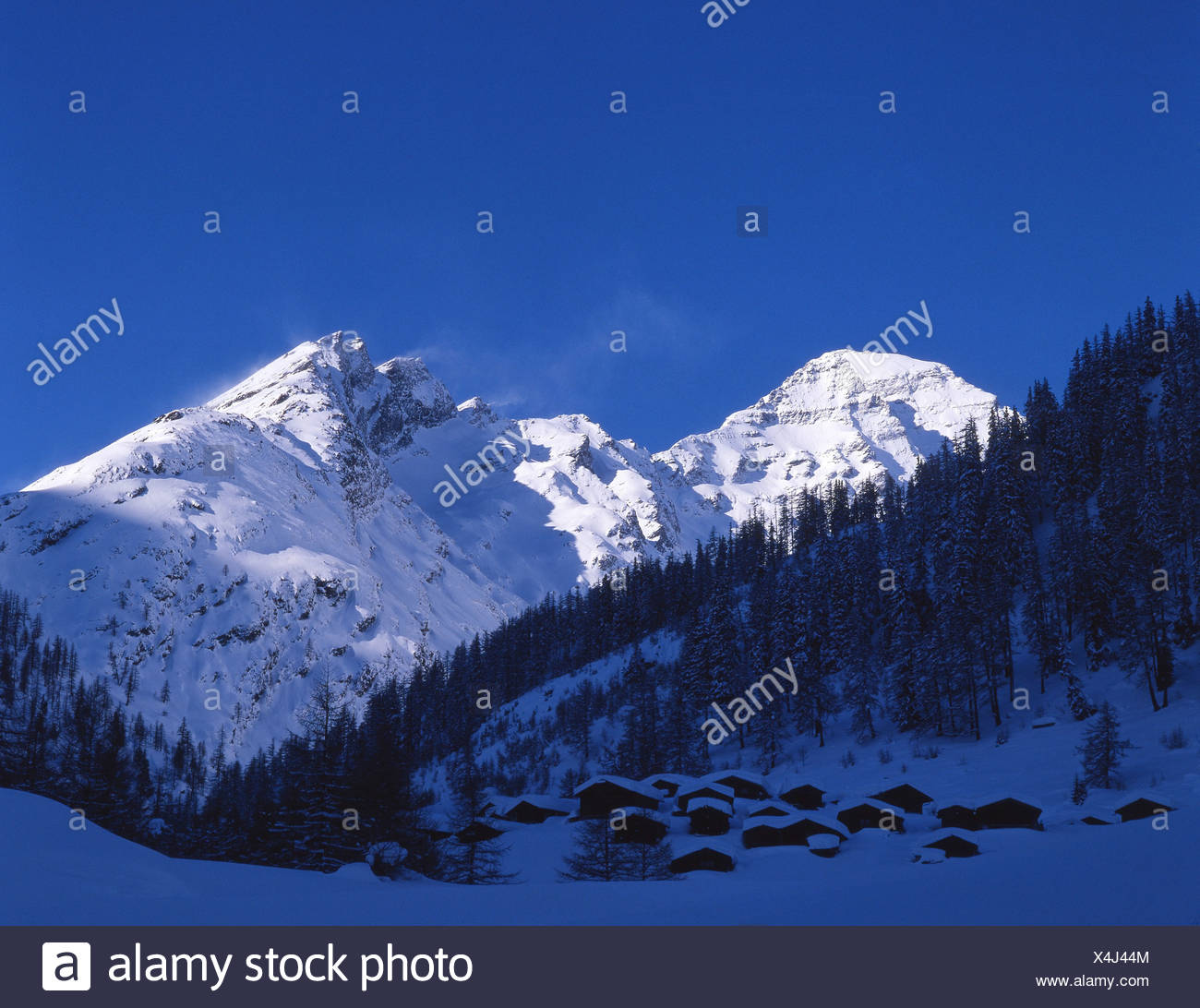 Lotschental Fafleralp hamlet settlement shade winter snow mountains Alps dusk twilight mood canton Valais - Stock Image