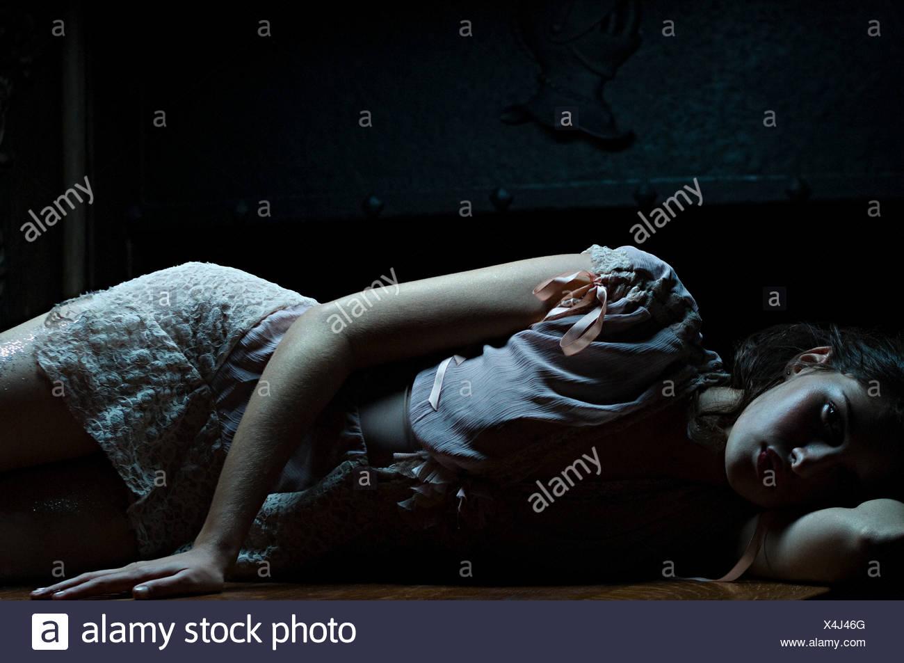 Woman lying is shadows - Stock Image