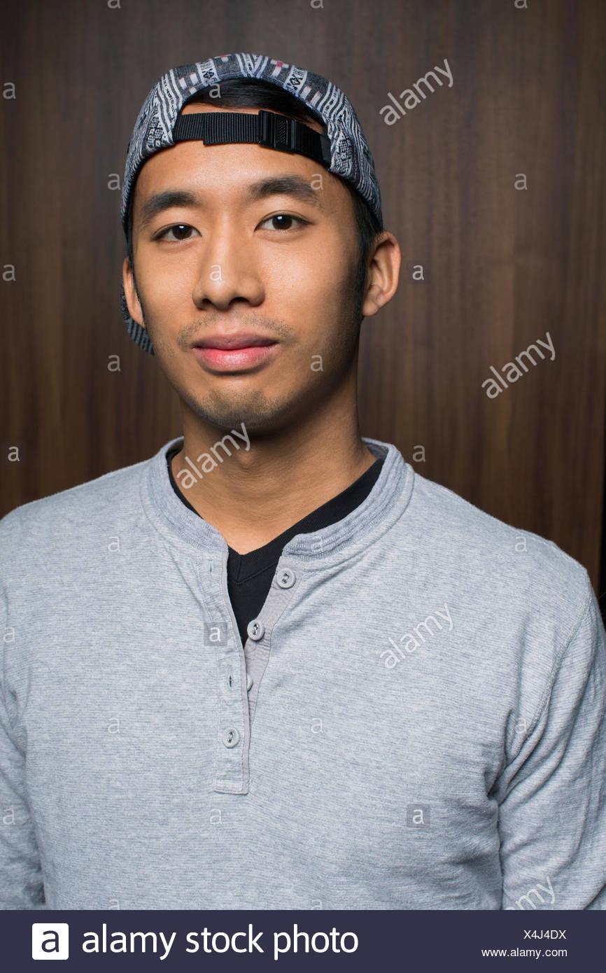 Portrait of smiling man wearing backward baseball cap - Stock Image