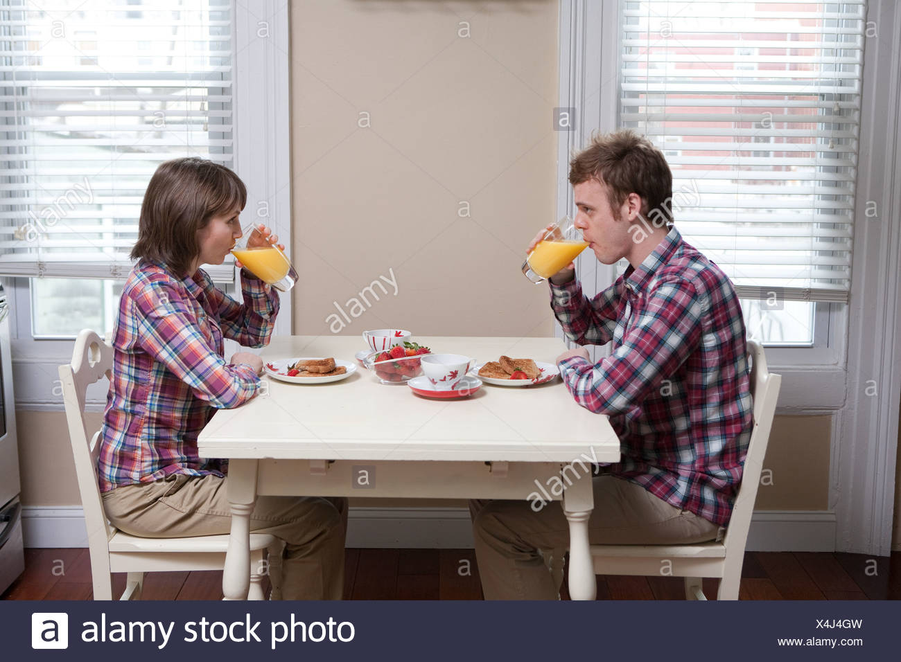 Young couple drinking orange juice at kitchen table - Stock Image