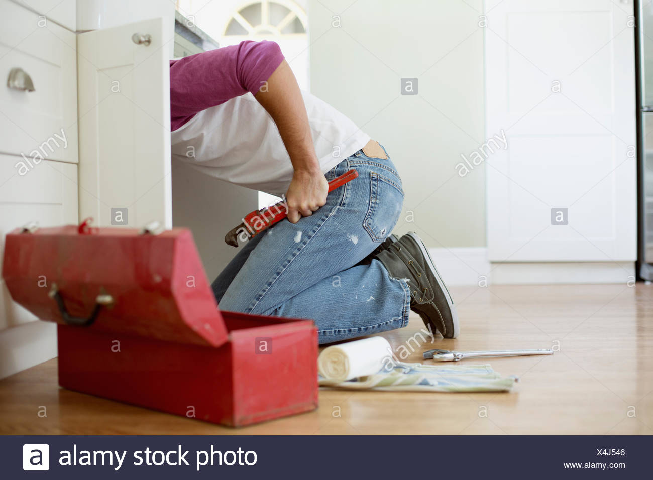 mid adult homeowner repairing plumbing under the sink - Stock Image