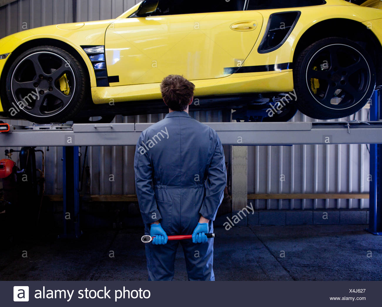 Male mechanic checking yellow sports car, holding socket wrench behind his back, rear view Stock Photo