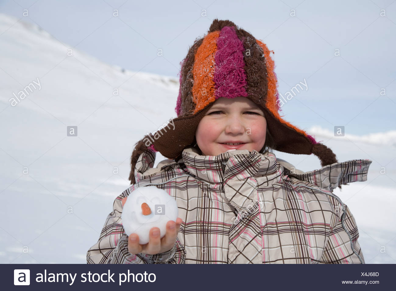 93d8244a198 Portrait of young girl holding snowball with smiley face and carrot nose -  Stock Image