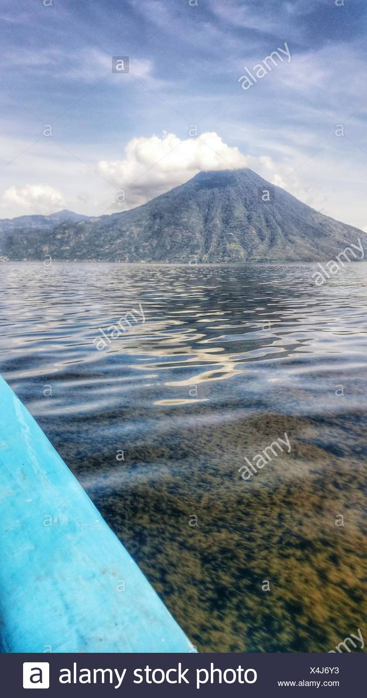 Lake Atitlan By Volcanic Mountain Against Sky - Stock Image