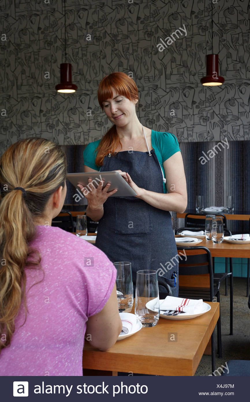 Mid adult woman using digital tablet in restaurant - Stock Image