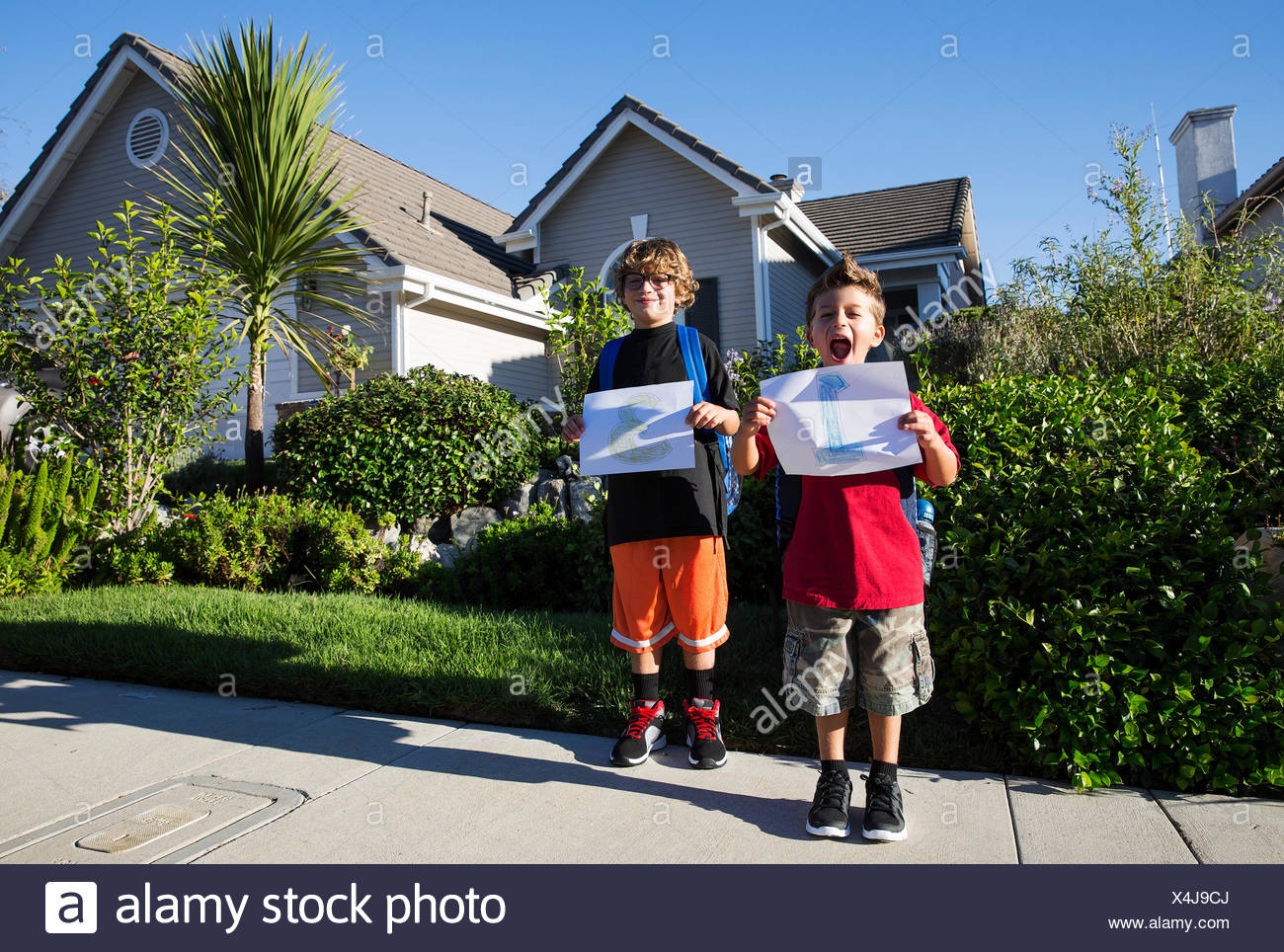 Portrait of two brothers holding up pieces of paper with 1 & 3 - Stock Image
