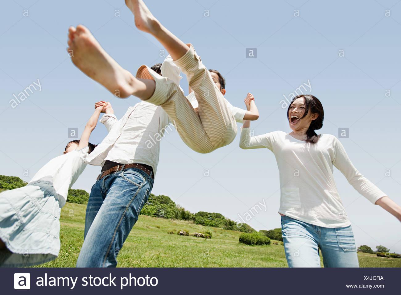 Parents lifting son mid air Stock Photo
