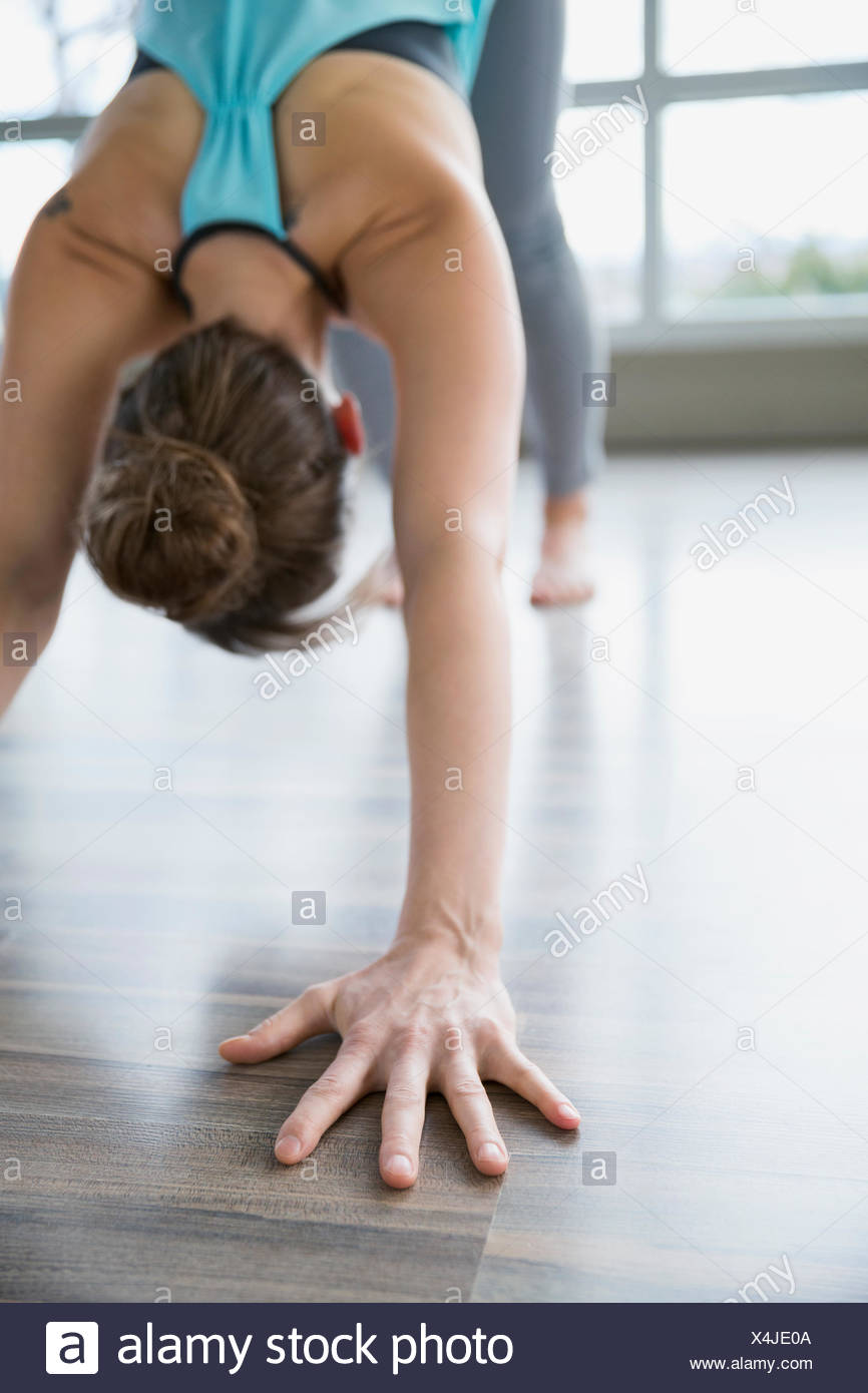 Woman practicing yoga in downward facing dog pose - Stock Image